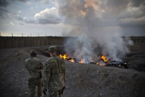 U.S. Army soldiers watch garbage burn in a burn-pit at Forward Operating Base Azzizulah in Maiwand District, Kandahar Province, Afghanistan, February 4, 2013. REUTERS/Andrew Burton (AFGHANISTAN - Tags: MILITARY) - RTR3DCLD