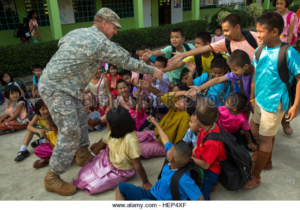 U.S. Army Chaplain, Capt. Ryan Mortensen, assigned to 1st Battalion, 27th Infantry Regiment, 2nd BCT, 25th Infantry Division, meets with local school children to learn about the difference in American and Thai culture during a humanitarian aid mission in Lopburi province, Thailand, Feb. 16, 2015. The mission was carried out as a part of the joint-training operation Cobra Gold 2015. (U.S. Army photo by Spc. Steven Hitchcock/Released) Cobra Gold 2015 150216-A-SE706-168